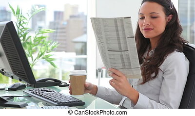 Businesswoman reading a newspaper while drinking coffee