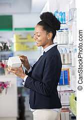 Businesswoman Reading Instructions On Medicine Box In Pharmacy