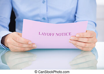 Businesswoman Reading Layoff Notice - Midsection of...