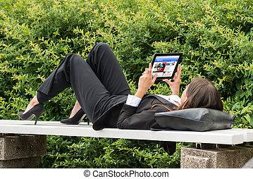 Businesswoman Reading News On Digital Tablet