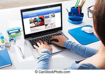Businesswoman Reading News On Laptop