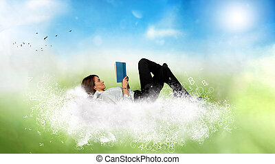 Businesswoman reads a book over a cloud made of letters. Concept of relax and imagination.