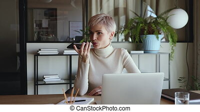 Young business woman holding smart phone recording audio message, speaking on speakerphone, using voice recognition virtual assistant mobile app in office. Digital search ai assistance tech concept