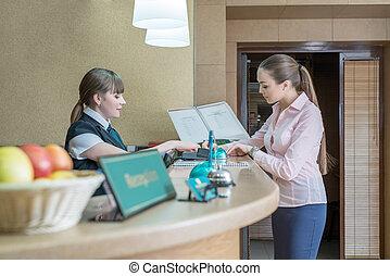 Businesswoman registers on arrival in hotel