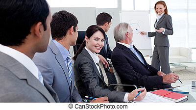 Businesswoman reporting sales figures to her team in the...