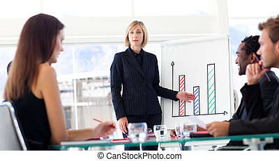 Businesswoman reporting to sales figures to her team in a...