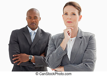 Businesswoman resting head on hand in front of businessman