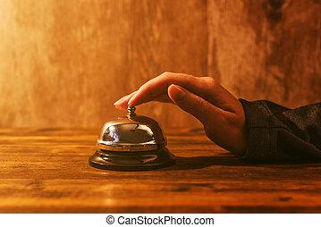 Businesswoman ringing hotel reception bell