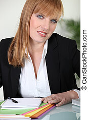 Businesswoman sat at desk doing paperwork