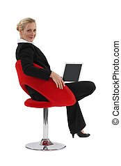 Businesswoman sat in designer chair with laptop