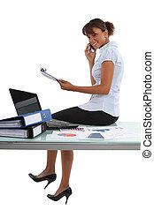 Businesswoman sat on desk whilst working