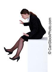 Businesswoman sat on ledge