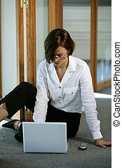 Businesswoman sat on the floor with laptop