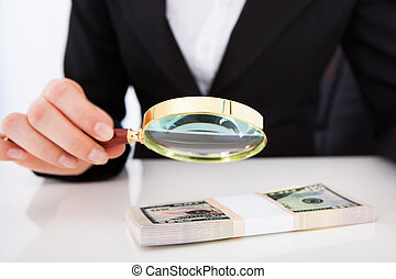Businesswoman Scrutinizing Dollar Bills With Magnifying Glass