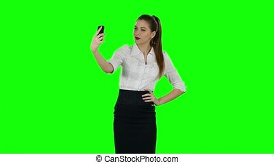 Businesswoman selfie with phone. Green screen