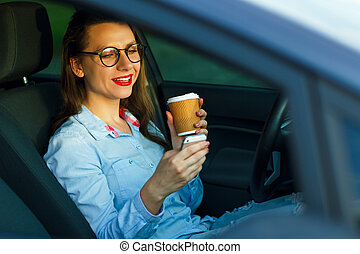Businesswoman sending a text message and drinking coffee while driving a car