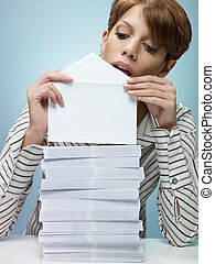caucasian secretary closing pile of envelopes. Vertical shape, front view, waist up, copy space