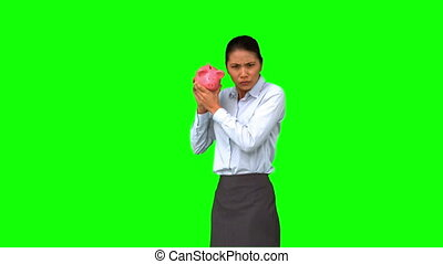 Businesswoman shaking an empty piggy bank on green screen in...