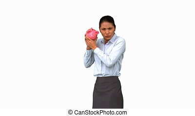 Businesswoman shaking an empty piggy bank on white screen in...