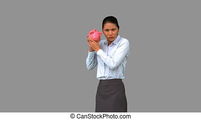 Businesswoman shaking an empty piggybank
