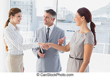 Businesswoman shaking co-workers hand