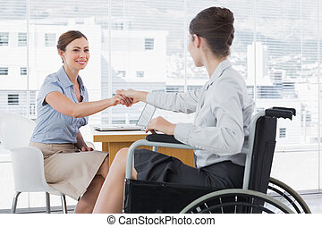 Businesswoman shaking hands with disabled colleague at desk...