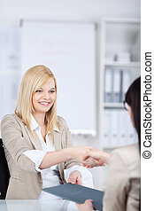 Businesswoman Shaking Hands With Female Candidate At Desk