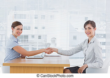 Businesswoman shaking hands with interviewee and both smiling at camera at desk in office