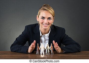 Businesswoman Sheltering Paper Team On Desk