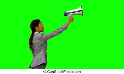 Businesswoman shouting into a megaphone on green screen in...