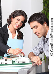 businesswoman showing a model of a house to a client
