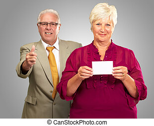 Businesswoman Showing Card In Front Of A Businessman Shaking Hand Isolated On Gray Background