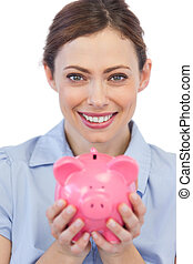 Businesswoman showing her piggy bank to camera