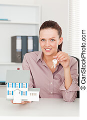Businesswoman showing keys and model house