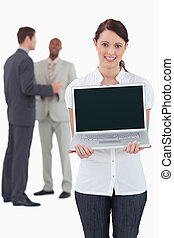Businesswoman showing laptop with colleagues behind her