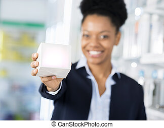 Businesswoman Showing Medicine Box In Pharmacy