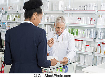 Businesswoman Showing Prescription To Chemist In Pharmacy