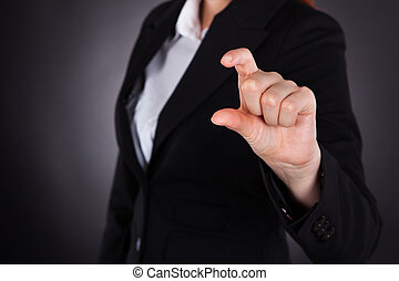 Businesswoman Showing Small Amount Gesture - Midsection of...