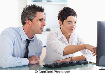 Businesswoman showing something on a screen to her colleague