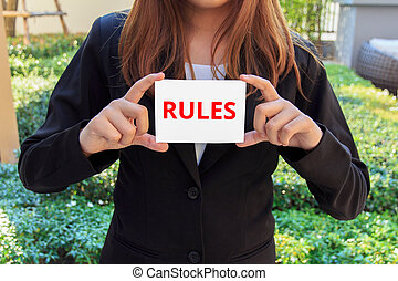Businesswoman showing white sign with Rules word