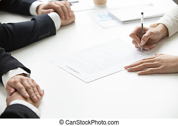 Businesswoman signing business document at group meeting, close