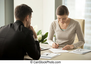 Businesswoman signing contract with businessman