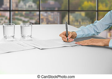 Woman signs contract at office.