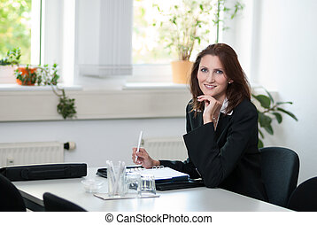 Businesswoman sits at a table