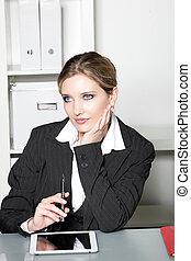 Businesswoman sitting at her desk thinking