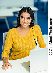 Businesswoman sitting at her workplace with headphones