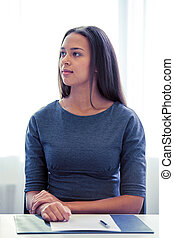 businesswoman sitting at table in office