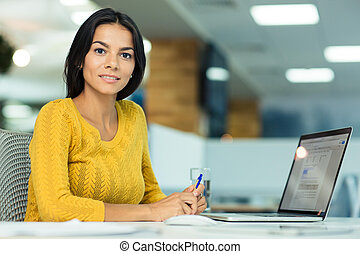 Businesswoman sitting at the table in office