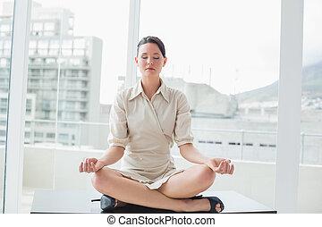 Businesswoman sitting in lotus posi