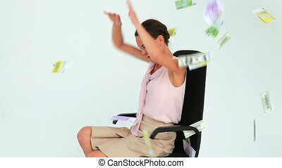 Businesswoman sitting on a chair with banknotes falling from the sky